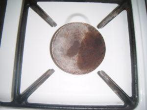 Nevyčištěný hořák s roštem na plynovém sporáku
